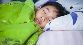 Healthy child. Little asian boy sleeping peacefully on bed in dark bedroom.